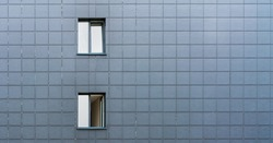 small windows with white skyscape reflections in local city building wall with grey tiles decorations on summer day