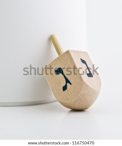 Small wood dreidel for Hanukkah on white background.