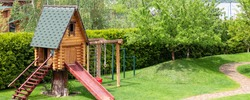 Small wood log playhouse hut with stairs ladder and wooden slide on children playground at park or house yard. Panoramic view. Green grass lawn garden and paved pathway background on bright sunny day