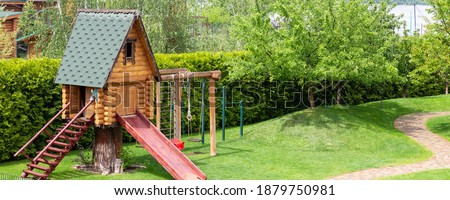 Small wood log playhouse hut with stairs ladder and wooden slide on children playground at park or house yard. Panoramic view. Green grass lawn garden and paved pathway background on bright sunny day ストックフォト ©