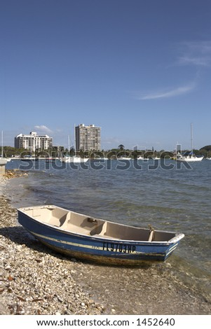 small wooden boat on the shoreline of island park with the skyline of sarasota in the background florida united states taken in march 2006