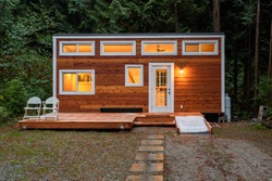 Small wooden cabin house in the evening. Exterior design.