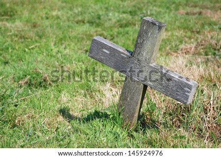 Small wooden cross in the grass of a graveyard