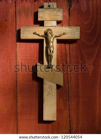 Small wooden crucifix hanging on wooden wall under beam of light