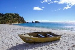 Small Wooden Fishing Boat on Sand on Beach. Sea, Rock, Trees and Hill in Background. Blue Sky with Clouds on Sunny Summer Day. Touristic Natural Environment with Nobody. Peaceful and Beautiful Image.