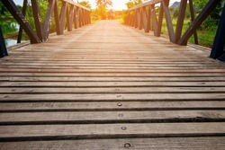 Small wooden foot bridge or walkway crossing over river and glowing light at the end of wooden ways. Perspective Outdoor Scene.