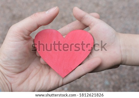 small wooden heart in the hand of a woman and a child. The concept is a mother's boundless love for a child, healing children, helping children. Horizontal photo, close-up Foto stock ©
