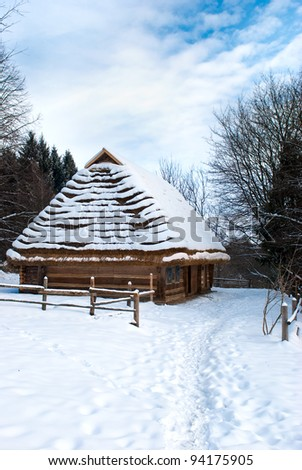 Small wooden houses in winter against blue sky