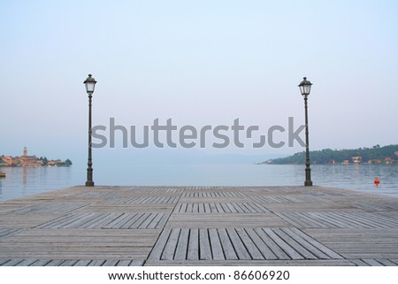 Small wooden idyllic pier in the lake. With lamp and nicely textured wooden surface on the foreground. A city and lake on the background. Garda lake, Salo village, Italy, Europe