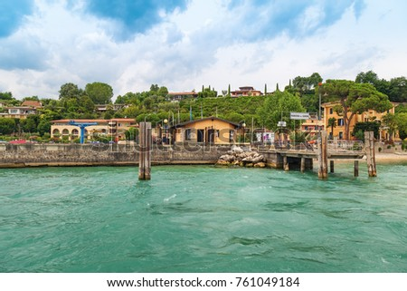 "Small wooden pier city of Manerba del Garda is a quiet resort town on the Western shore of lake Garda. The view from the water on small Italian city. ""Manerba del Garda"" is name city. #761049184"