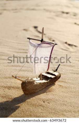 small wooden ship toy model in the sand on the beach