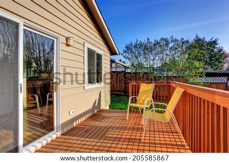 Small wooden walkout deck with two yellow chairs #205585867