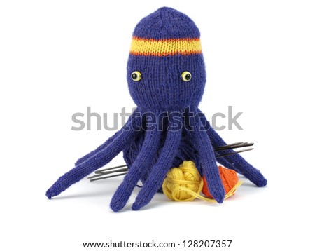 small wool balls, needles and knitting octopus on a white background