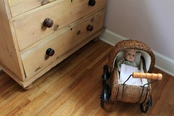 Small woven baby carriage with fake baby inside a play room with wooden floors and cabinets.