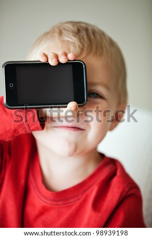 small 3 year old toddler boy holding his media player with empty screen in his hand