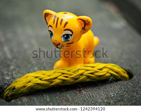 Small yellow toy tiger behind rope on wooden table with blurred background Zdjęcia stock ©
