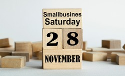 SMALLBUSINESS SATURDAY is written on wooden cubes stacked in the form of a mobile calendar.