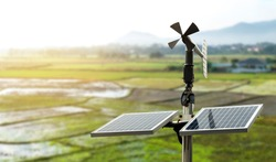 Smart agriculture and smart farm technology concept. Revolving vane anemometer, a meteorological instrument used to measure the wind speed and solar cell system with rice field background.