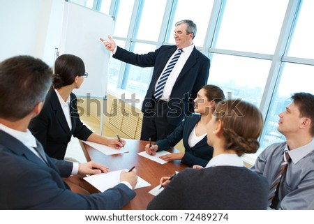 Smart and confident boss pointing at whiteboard while making presentation