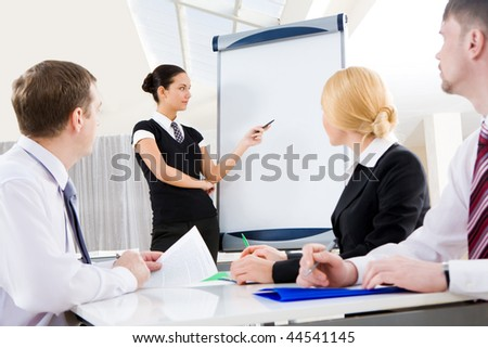 Smart and confident employee pointing at whiteboard while presenting her ideas