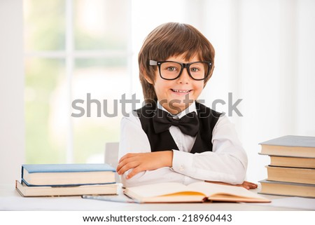 Smart and confident schoolboy. Cute young boy keeping arms crossed while sitting at the table