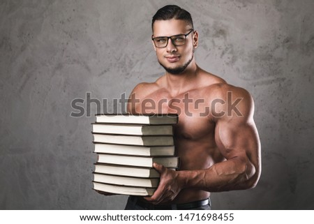 Smart and muscular man with a heap of books. Concept of knowledge in bodybuilding.