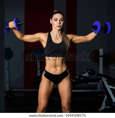 Smart and powerful woman standing and training in gym wearing only black panties and black sport bra. She holds two big barbells and shows fitness exercises. Fitness concept.