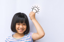 Smart asia kid hold LED bulb in her hand. Happy smiley asian girl child having an Idea concept on white background.Positive Thinking. Universal Children's Day.World Thinking Day