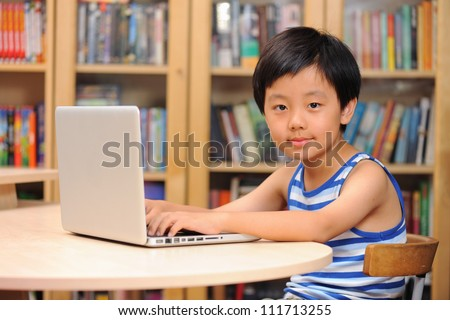 Smart Asian boy working on a laptop computer