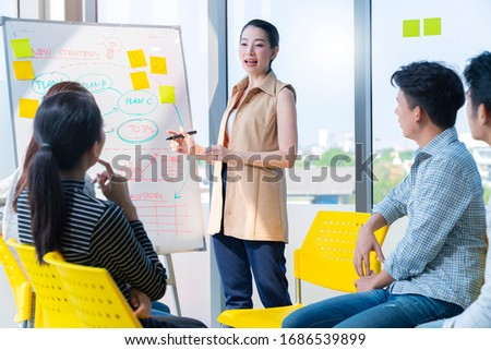 smart asian business female leader in a casual meeting with her teamwork colleagues at the modern desogn office presenting sales strategy plan and data or forecast for a project goal schedule