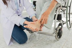 smart asian doctor holding leg of old stroke patient in hospital, elderly rehabilitation clinic, they training to rehab muscle, chronic ankle pain