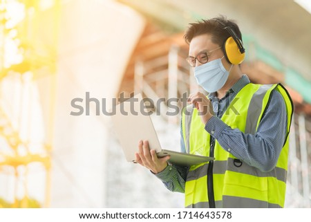 smart asian male wearing protection face mask professional civil engineer hand hold laptop site construction check with infastrcture and building background
