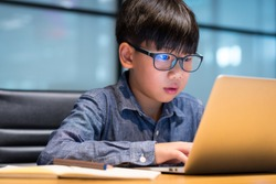 Smart asian preteen boy wearing blue light blocking glasses using his laptop to study lesson through online learning from home during Covid-19 pandemic, city lockdown and social distancing.