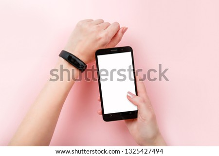 Smart Band App Mobile Phone Sport bracelet and smartphone with white screen mock up. Fitness band run tracker on woman's hand. wristband with running activity steps counter and heartbeat pulse meter #1325427494