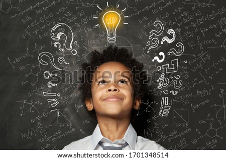 Smart black kid with lightbulb. Brainstorming and idea concept. Little student boy on chalkboard background