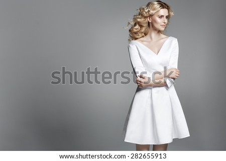 Smart blond lady wearing white dress