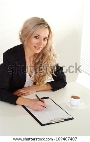 Smart blonde is hard  working in her office