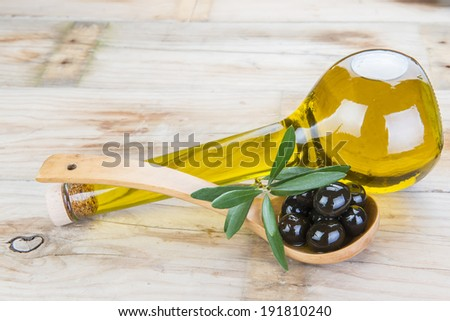 Smart bottle of olive oil and wooden spoon with black olives