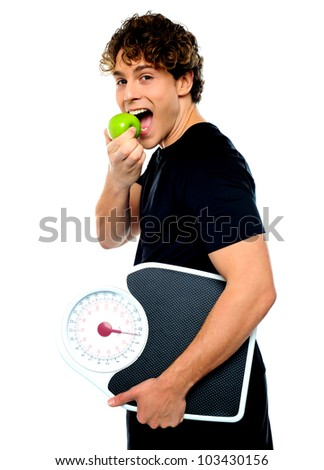 Smart boy eating green apple with scale in his other hand