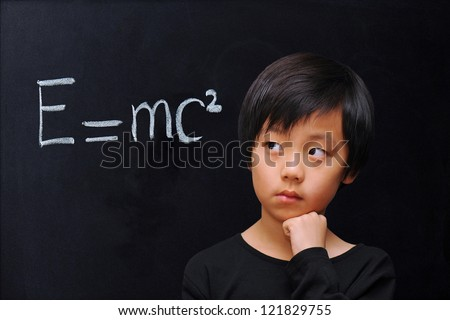 Smart boy in front of blackboard with physics formula