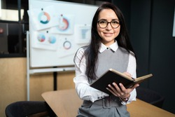 smart brunette woman of Caucasian appearance with glasses, a white shirt. a Manager in the banking sector works remotely remotely from home makes tasks plans strategy records for new projects