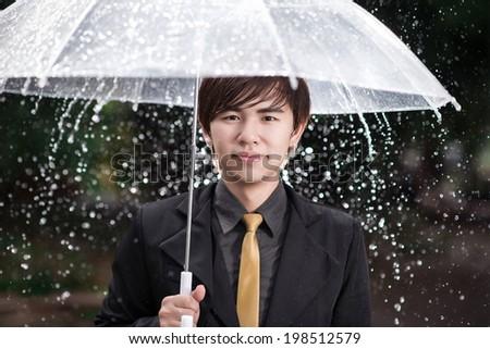 Smart business man holding umbrella among the rain