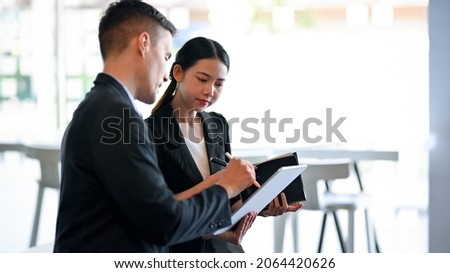 Smart businessman discuss and explain new business marketing strategy to his team. businesswoman looking on tablet screen with her colleague.