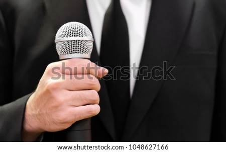 Smart businessman, good looking man in black suit speech and speaking with microphone, talk show, seminar spokesman, master of ceremonies. Businessman Suit holding microphone #1048627166