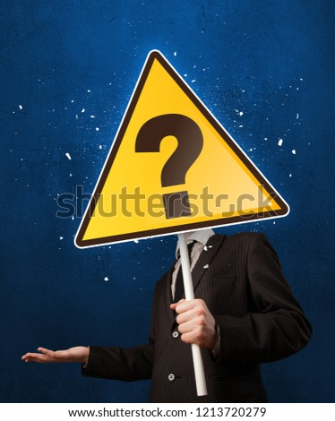 Smart businessman holding yellow sign with question mark #1213720279