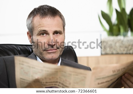 Smart businessman sitting in office chair reading newspaper and looking straight.