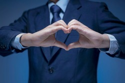 Smart Businessman wear blue suit shirt and tie making heart shape by his hand on blue background. Handsome man show heart symbol, love icon for Business lover, I love my job, take care service concept