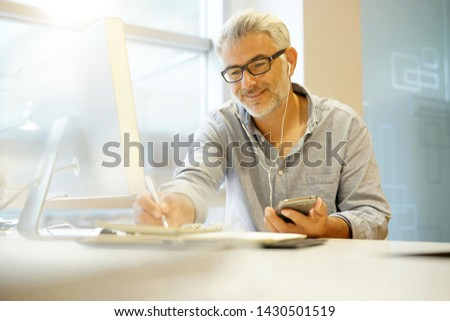 Smart casual businessman working with headphones in modern office #1430501519