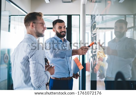 Smart casual businessmen discussing organisation plan from board during working time in company, happy Caucasian male employees creating productive strategy while analyzing information indoors Photo stock ©
