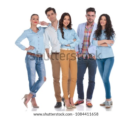 smart casual group of five people standing on white background, with two men in the middle of the women. They are wearing blue shirts and jeans and one man is wearing glasses. #1084411658